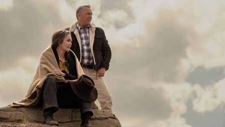 "Diane Lane as ""Margaret Blackledge"" sits on a rock with Kevin Costner (right) as ""George Blackled standing"