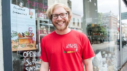 A man with ginger hair, Rollo, smiling with a red t-shirt on.