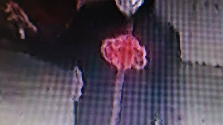 The masked figure who sprayed racist graffiti on a Swiss Cottage wall. Picture: Met Police