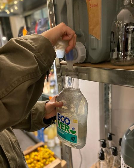 A hand squirting liquid from a tank into an empty Ecover bottle.