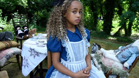 Keira Chansa with hair in ringlets at outdoor tea party as Alice Littleton