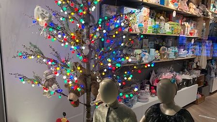 Mannequins of children in a shop window, in front of a Christmas trees with colourful lights