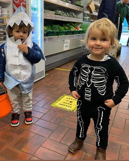 Two children in fancy dress - one as a skeleton and one as a shark - smiling into the camera.