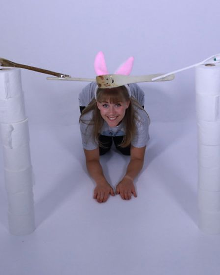 A woman crouching on the floor, wearing bunny ears, and next to two stacks of toilet roll.