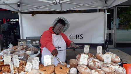 A woman in front of a market stall selling bread.