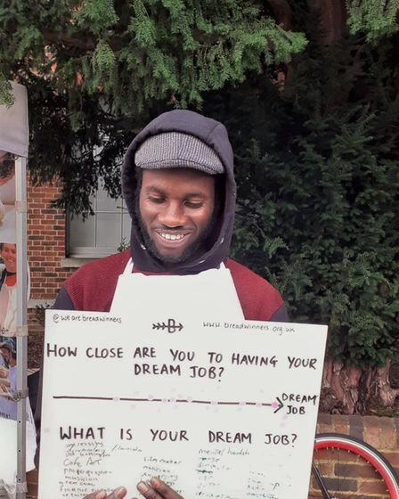 """A man holding a sign reading: """"How close are you to having your dream job?"""""""