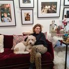 A woman with a white dog on a red sofa.