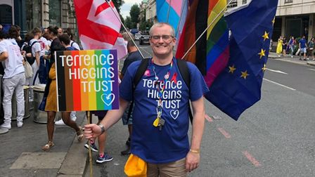 """Man, Eugene Lynch, standing in the road, smiling, with a number of flags on his back and a rainbow sign reading """"Terrence..."""
