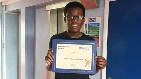 Emmanuel Toko holding his Jack Petchey Foundation achievement award in the corridor at Forest Gate School.