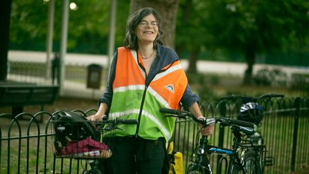 Woman in a high vis jacket leaning on a fence with a bike.