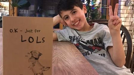 A young boy doing a thumbs up next to a book, with the title OK-Just for Lols