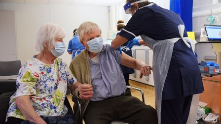 Carole Smith, 82, holds her husband, 86-year-old Tony's hand as he has his Covid-19 vaccination at t