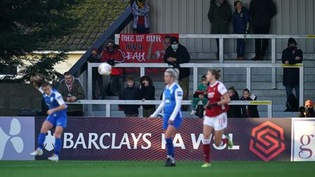 Arsenal fans watch on from the stands during the FA Women's Super League match at Meadow Park, Londo