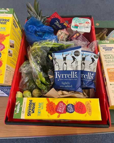 A red box of vegetables, crisps and cereal.