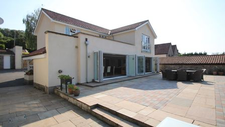 back of large detached cream rendered house with huge beige paved terrace outside of two sets of bi-folding doors and...