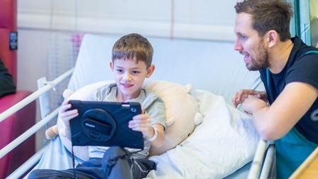 Child in hospital bed watches theatre on a tablet as stage manager looks on