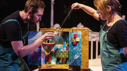 Two Little Angel puppeteers manipulate a puppet in a colourful box