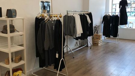 The inside of a clothes shop, with racks of black and white garments.