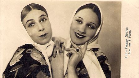 Sepia image of two young women, tilting heads together in headscarves