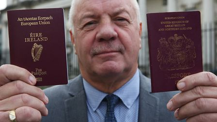 Raymond McCord holds up his newly issued Irish passport. Photograph: Brian Lawless/PA.