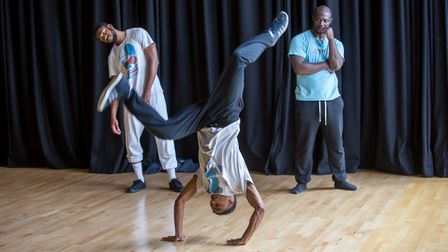 Man performs handstand dance while two men watch at East London Dance.