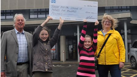 Emelia and Isabel Andrew present their cheque for £500 to League of Friends secretary Philip White a