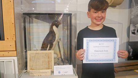 Emerson Ives standing by his adopted penguin at Torquay Museum