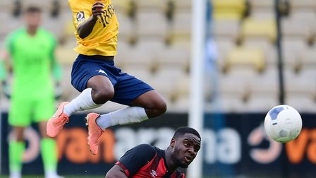 Aaron Nemane of Torquay United leaps the challenge from Christian Sayde of Bournemouth under-23s dur
