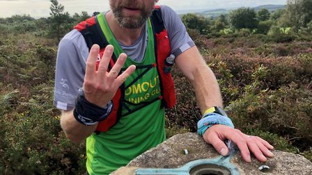 Sidmouth Running Club member Ross Walton at Trig number four during the Climb South West 8 Trigs rac