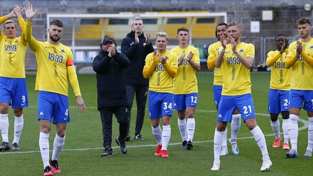 The Torquay squad applaud the fans watching online before during the match between Torquay United an