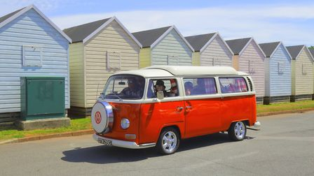 Staycations... a classic Volkswagen camper van with beach huts in background near Broadsands Beach, Paignton