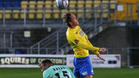 Asa Hall beats Matt Rhead of Boreham Wood to the header during the match between Torquay United and