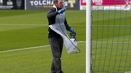 A Covid official sprays the post during the pre-season match between Torquay United and Chippenham T