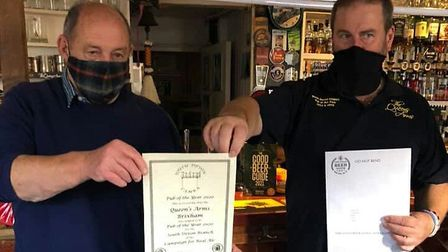 Queens Arms landlord Chris Simmonds (right) accepts the award from South Devon CAMRA chairman Bob So