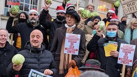A group of anti-LTN protesters outside Hackney Town hall waving cabbages.