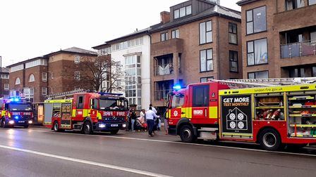 Fire engines and firefighters attend the scene of a flat fire while evacuated residents look on as the incident unfolds