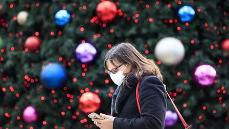 A woman walks past a Christmas tree in Trinity Leeds shopping centre in Leeds, Yorkshire, as England