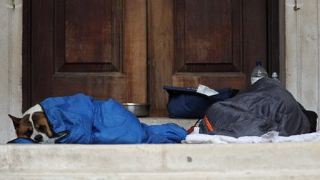 A homeless person and their dog shelter in a doorway in separate sleeping bags in London. Picture: