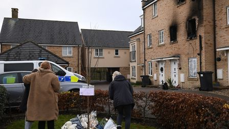 People lay flowers at the scene of a house fire on Buttercup Avenue, Eynesbury, Cambridgeshire, in which a three-year-old boy...