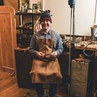 Shop owner and jeweller Roger Taylor sitting and smiling at his work station where he makes jewellery