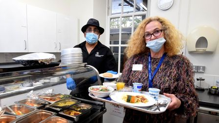 Volunteer Nadya Lurie collects patients' lunch orders from Jacob Pereire of the St John's Hospice ca