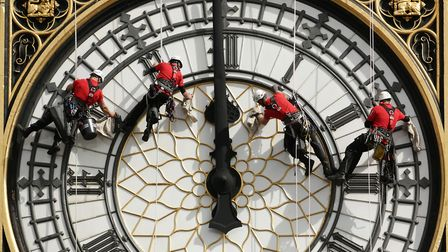 A specialist technical abseil team clean and inspect one of the four faces of the Great Clock, other