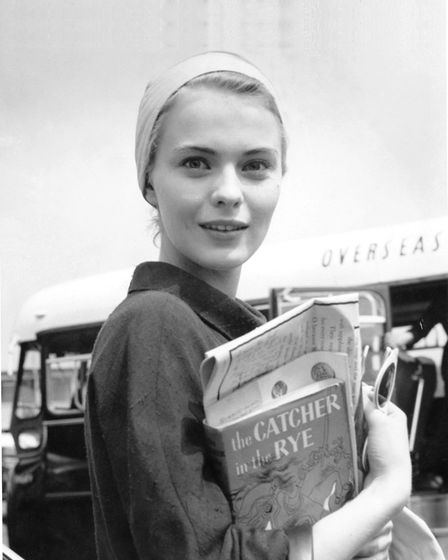 American actress Jean Seberg (1938 - 1979) arrives at an airport carrying a copy of the book 'The Ca