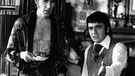 British actor Dudley Moore pointing something to British actor Peter Cook wearing dressing gown and