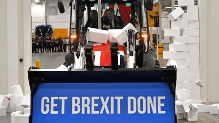 """Boris Johnson drives a union flag-themed JCB, with the words """"Get Brexit Done"""" inside the digger buc"""