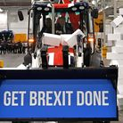 """Boris Johnson drives a union flag-themed JCB, with the words """"Get Brexit Done"""" inside the digger bucket"""