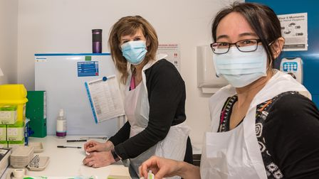 Two medical staff wearing blue face masks and PPE aprons prepare the doses of the Covid-19 vaccination for the patients