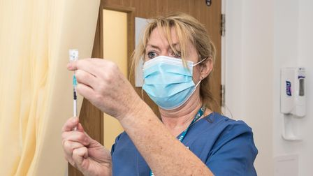 A medical worker at Stansted Surgery wearing a blue face mask loads a needle with the Covid-19 vaccine
