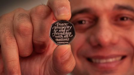 Chancellor Sajid Javid holding the Brexit coin, a 50p bearing the inscription 'Peace, prosperity and