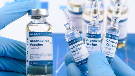 Image showing hands wearing disposable gloves holding coronavirus vaccine vials
